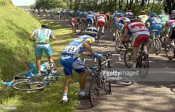 Germanys Andreas Kloden lays on the ground after a fall as the pack rides by during the fifth stage of the 94th Tour de France cycling race between...