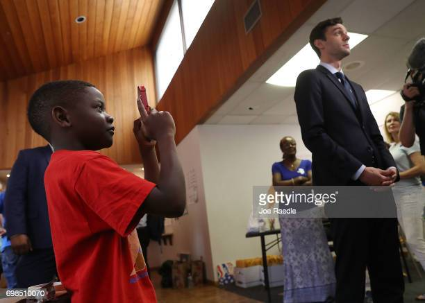 Chace Mallory takes a picture as Democratic candidate Jon Ossoff speaks to the media during a visit to a campaign office on election day as he runs...