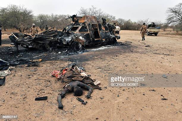 Chad army soldiers look at a burnt out rebel vehicle on May 8 2009 in the area of Am Dam 130 km south of Abeché where fighting took place on May 7...