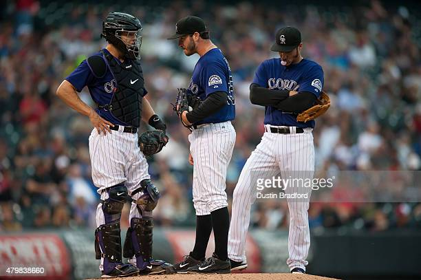 Chad Bettis of the Colorado Rockies waits on the mound with Nick Hundley and Nolan Arenado before being relieved in the third inning of a game at...
