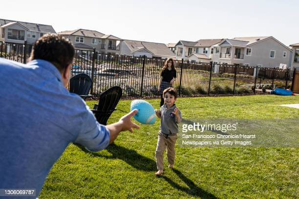 Chad Bourdon, director of operations and partner at San Francisco restaurant 25 Lusk, left, plays a game of catch with son Marc center, and daughter...