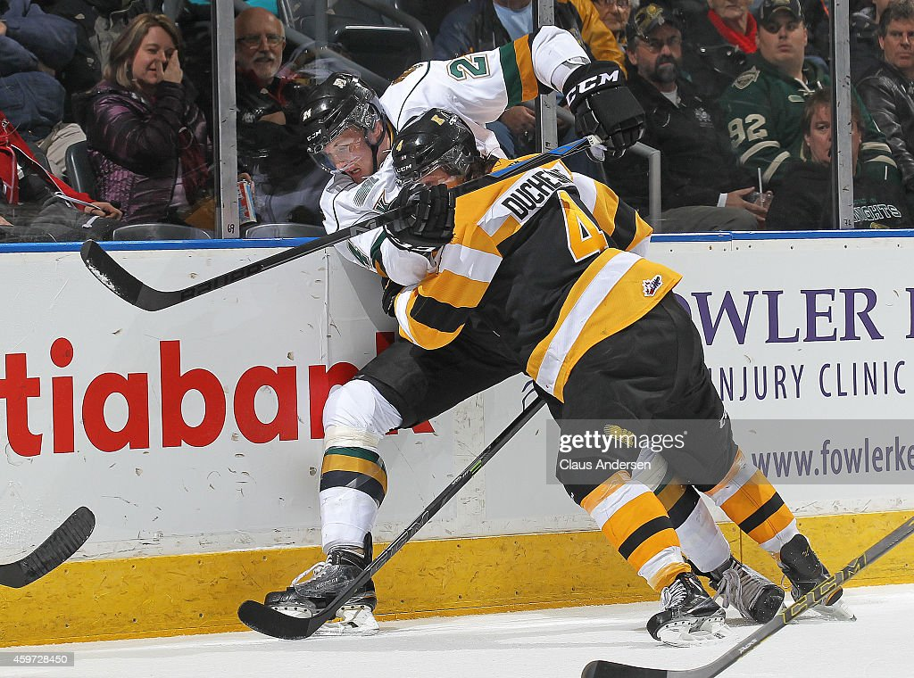 Chad Duchesne #4 of the Kingston Frontenacs takes Michael McCarron #24 of the London Knights into the boards in an OHL game at Budweiser Gardens on November 29, 2014 in London, Ontario, Canada. The Frontenacs defeated the Knights 3-2 in an overtime shoot-out.