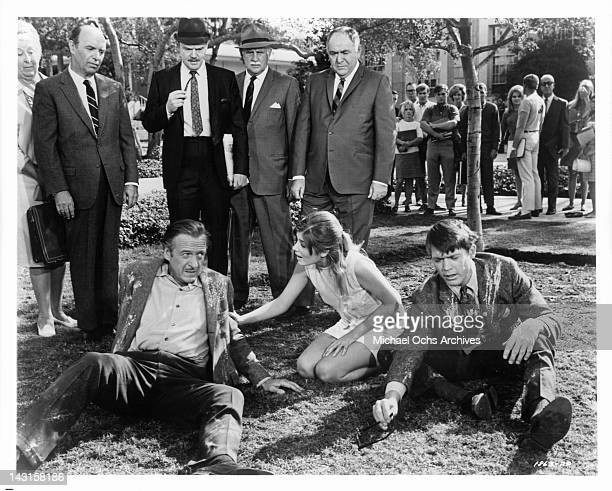 Chad Everett and David Niven gets placated by Cristina Ferrare in a scene from the film 'Impossible Years' 1968