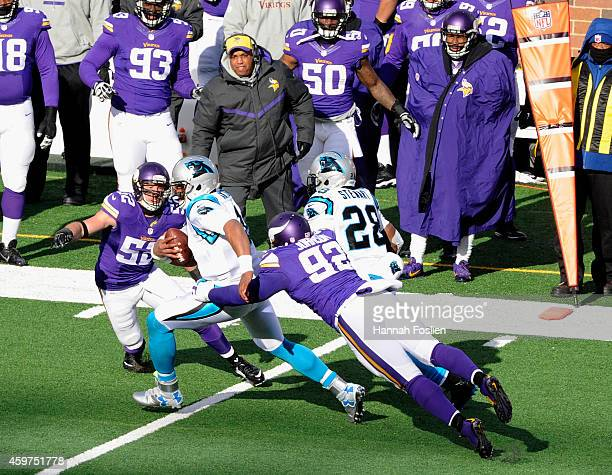 Chad Greenway and Tom Johnson of the Minnesota Vikings tackle Cam Newton of the Carolina Panthers during the first quarter of the game on November 30...