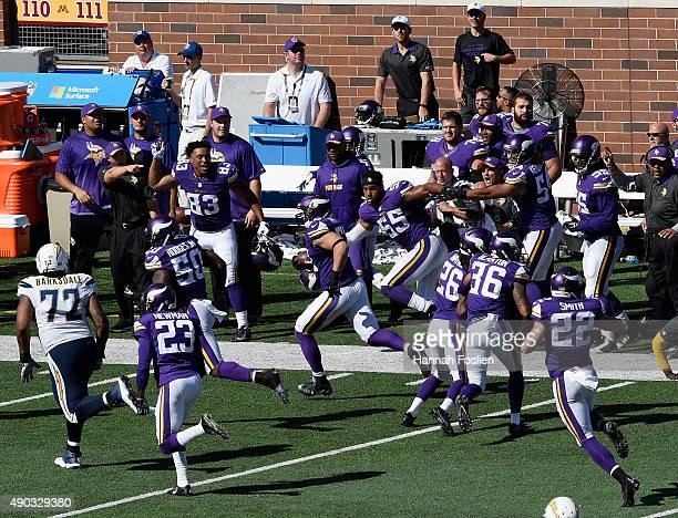 Chad Greenway of the Minnesota Vikings carries the ball past the Minnesota Vikings bench against the San Diego Chargers during the fourth quarter of...