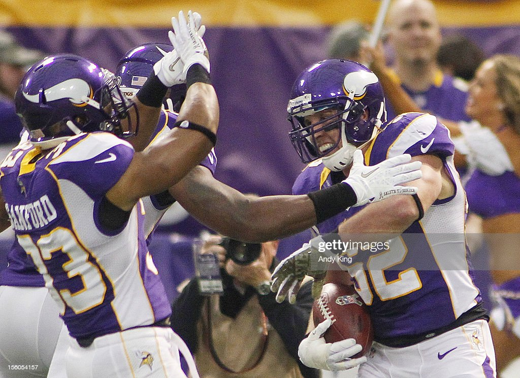 Chad Greenway #52 of the Minnesota Vikings is congratulated by teammates after intercepting a pass by Matthew Stafford #9 of the Detroit Lions in the first quarter on November 11, 2012 at Mall of America Field at the Hubert H. Humphrey Metrodome in Minneapolis, Minnesota.The Vikings defeated the Lions 34-24.