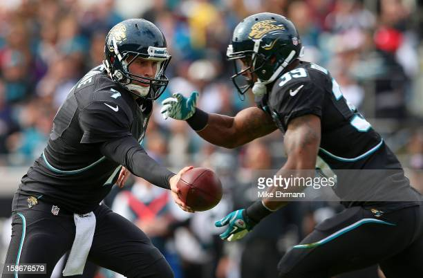 Chad Henne hands off to Richard Murphy of the Jacksonville Jaguars during a game against the New England Patriots at EverBank Field on December 23...