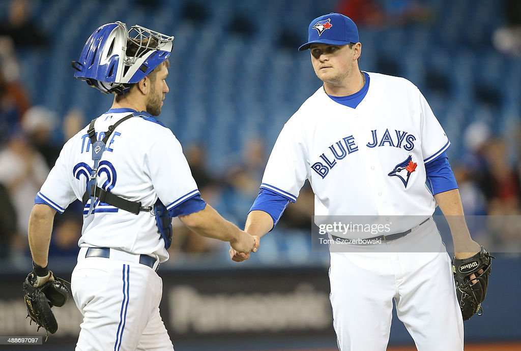 Chad Jenkins #64 of the Toronto Blue Jays celebrates their victory with Josh Thole #22 during MLB game action against the Philadelphia Phillies on May 7, 2014 at Rogers Centre in Toronto, Ontario, Canada.