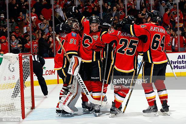 Chad Johnson and teammates of the Calgary Flames celebrate a win against the Minnesota Wild during an NHL game on December 2 2016 at the Scotiabank...