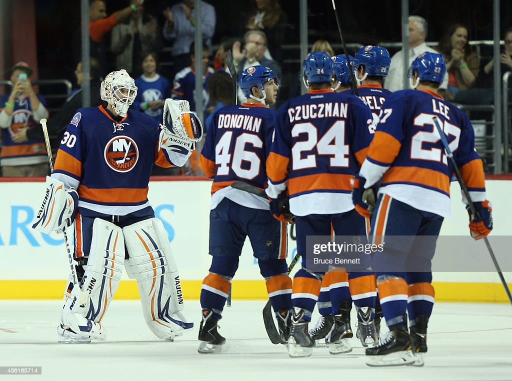 Chad Johnson #30 and the New York Islanders celebrate a 3-2 shootout victory over the New Jersey Devils at the Barclays Center on September 26, 2014 in the Brooklyn borough of New York City.
