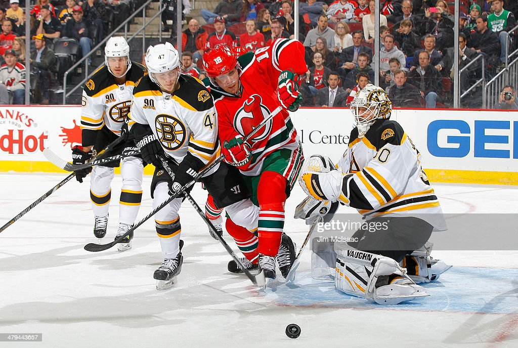 Chad Johnson #30 and Torey Krug #47 of the Boston Bruins defend a scoring chance in the second period against Steve Bernier #18 of the New Jersey Devils at the Prudential Center on March 18, 2014 in Newark, New Jersey.