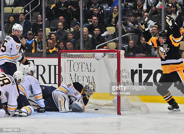 Chad Johnson of the Buffalo Sabres lets the puck into the net as Sidney Crosby of the Pittsburgh Penguins celebrates during the game at Consol Energy...