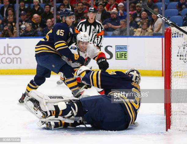 Chad Johnson of the Buffalo Sabres makes a save against Garnet Hathaway of the Calgary Flames as Brendan Guhle defends during the first period at...