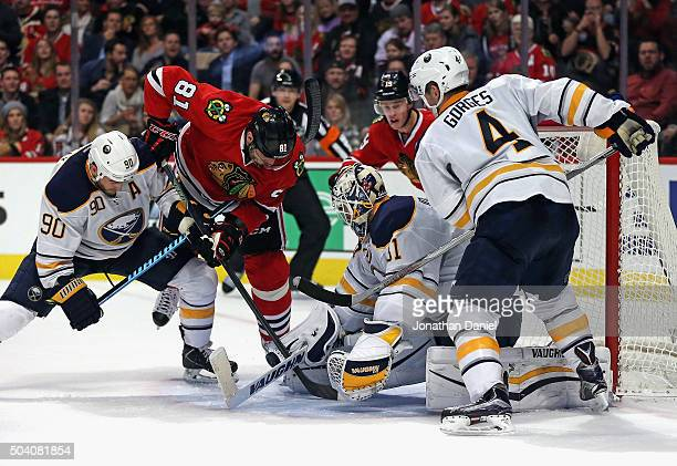 Chad Johnson of the Buffalo Sabres makes a save on a shot by Marian Hossa of the Chicago Blackhawks as Ryan O'Reilly and Josh Gorges defend at the...
