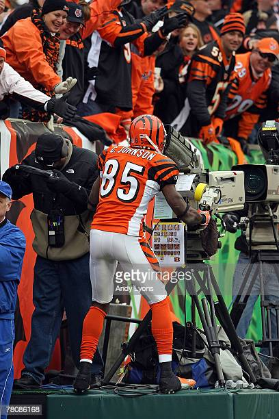 Chad Johnson of the Cincinnati Bengals celebrates after catching a touchdown pass by taking over a television camera during the NFL game against the...