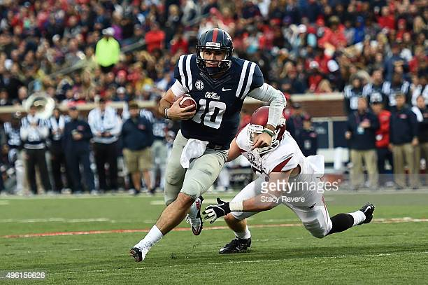 Chad Kelly of the Mississippi Rebels avoids a tackle by Brooks Ellis of the Arkansas Razorbacks during the second quarter of a game at...