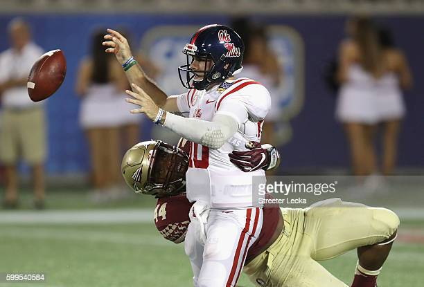 Chad Kelly of the Mississippi Rebels fumbles the ball as he is sacked by DeMarcus Walker of the Florida State Seminoles in the third quarter during...