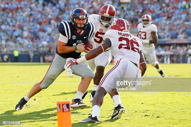 Chad Kelly of the Mississippi Rebels rushes as Marlon Humphrey and Dalvin Tomlinson of the Alabama Crimson Tide attempt to tackle him at...