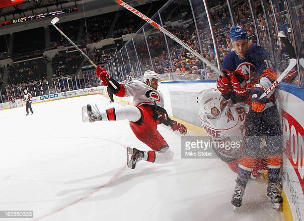 Chad LaRose and Alexander Semin of the Carolina Hurricanes fall to the ice behind Marty Reasoner of the New York Islanders at Nassau Veterans...