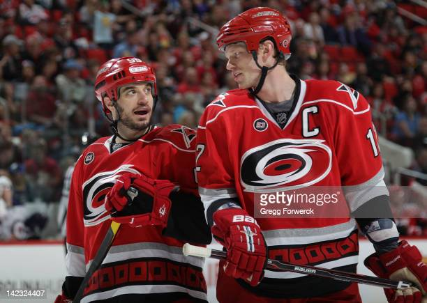 Chad LaRose and teammate Eric Staal of the Carolina Hurricanes converse prior to a faceoff against the Winnipeg Jets during an NHL game on March 30...