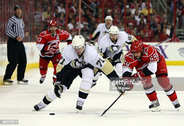 Chad LaRose of the Carolina Hurricanes battles for the puck against Evgeni Malkin of the Pittsburgh Penguins during Game Four of the Eastern...