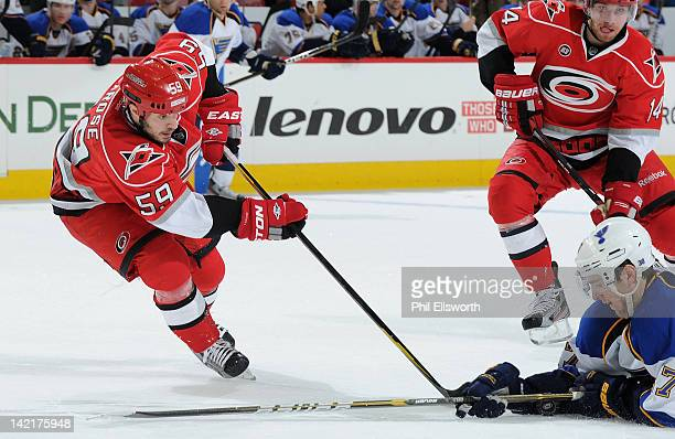 Chad LaRose of the Carolina Hurricanes can't get the puck past Ryan Reaves of the St Louis Blues during an NHL game on March 15 2012 at PNC Arena in...