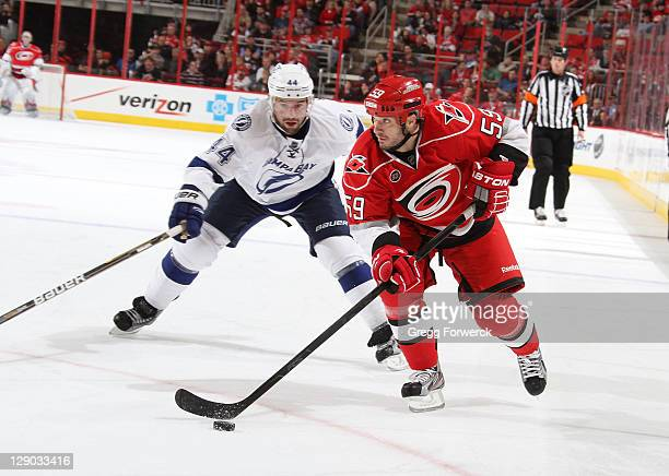 Chad LaRose of the Carolina Hurricanes carries the puck past Nate Thompson of the Tampa Bay Lightning during a NHL game on October 7 2011 at RBC...