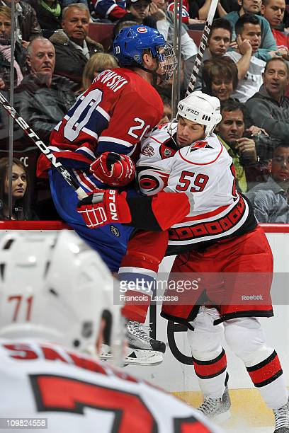 Chad LaRose of the Carolina Hurricanes checks James Wisniewski of the Montreal Canadiens into the boards during the NHL game on February 26 2011 at...