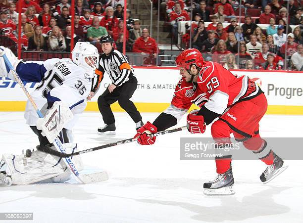 Chad LaRose of the Carolina Hurricanes gets a breakaway and lifts the puck past Dwayne Roloson of the Tampa Bay Lightning during a NHL game on...