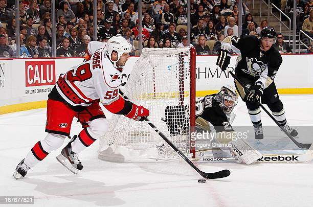 Chad LaRose of the Carolina Hurricanes moves the puck in front of MarcAndre Fleury and Paul Martin of the Pittsburgh Penguins on April 27 2013 at...