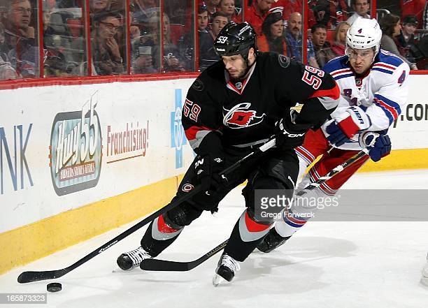 Chad LaRose of the Carolina Hurricanes protects the puck from Michael Del Zotto of the New York Rangers during their NHL game at PNC Arena on April 6...