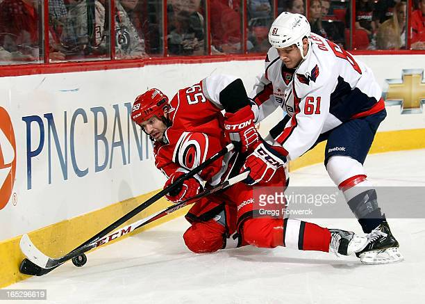 Chad LaRose of the Carolina Hurricanes tries to play the puck from his knees while being pressured by Steve Oleksy of the Washington Capitals during...