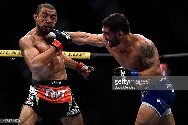 Chad Mendes of the United States punches Jose Aldo of Brazil in their featherweight championship bout during the UFC 179 event at Maracanazinho on...