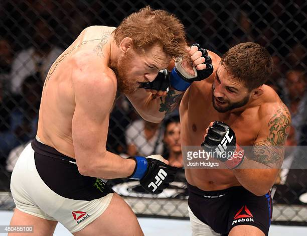 Chad Mendes punches Conor McGregor in their UFC interim featherweight title fight during the UFC 189 event inside MGM Grand Garden Arena on July 11...