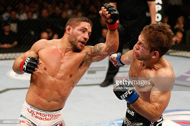 Chad Mendes punches Nik Lentz in their featherweight bout during the UFC on FOX event at Sleep Train Arena on December 14 2013 in Sacramento...