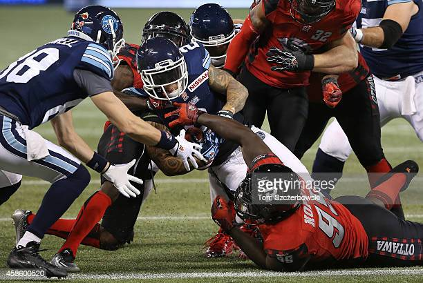 Chad Owens of the Toronto Argonauts breaks the plane with the ball to score a touchdown during CFL game action against the Ottawa Redblacks on...