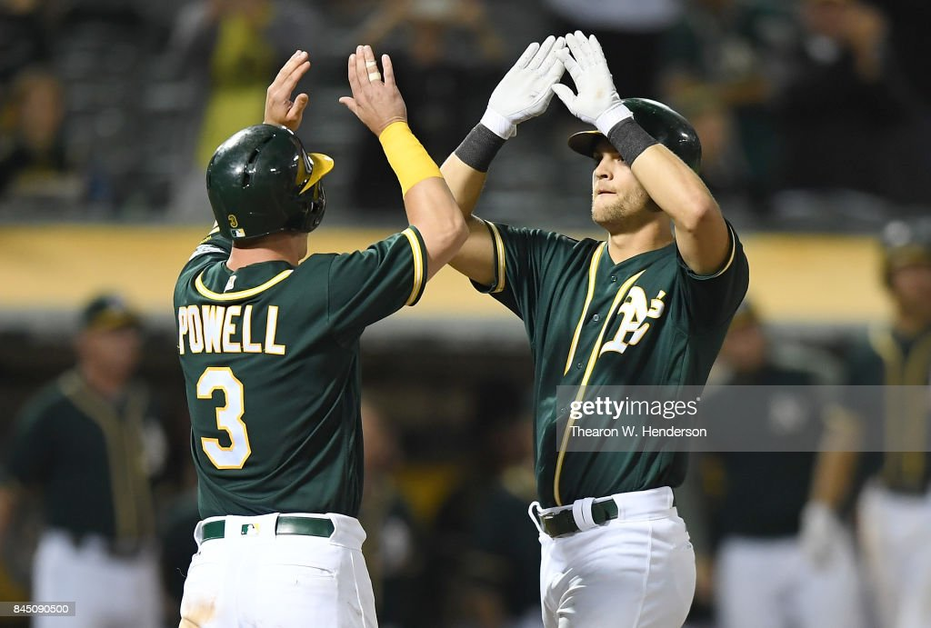 Chad Pinder #18 and Boog Powell #3 of the Oakland Athletics celebrates after Pinder hit a three-run homer against the Houston Astros in the bottom of the eighth inning of the second game in a double header at Oakland Alameda Coliseum on September 9, 2017 in Oakland, California.