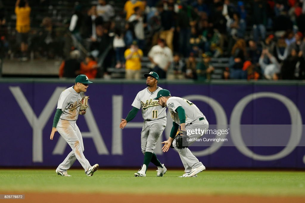 Chad Pinder #18, Matt Joyce #23 and Rajai Davis #11 of the Oakland Athletics celebrate a win against the San Francisco Giants in an interleague game at AT&T Park on August 2, 2017 in San Francisco, California.