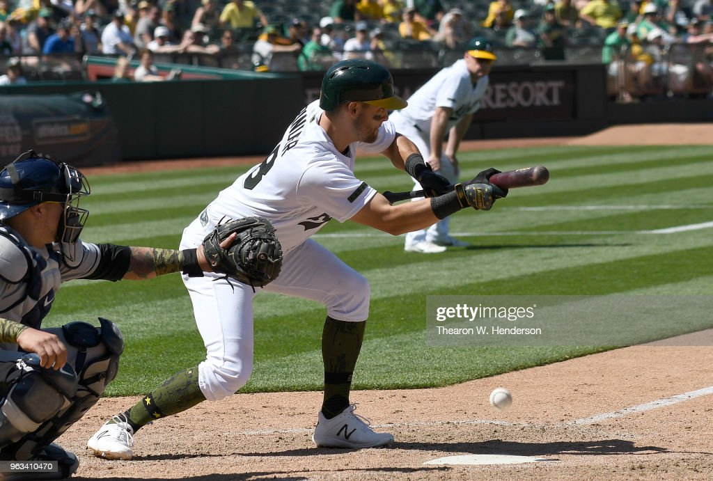 Chad Pinder #18 of the Oakland Athletics bunts against the Tampa Bay Rays in the bottom of the ninth inning at the Oakland Alameda Coliseum on May 28, 2018 in Oakland, California.