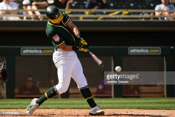 Chad Pinder of the Oakland Athletics hits a two run double against the Colorado Rockies in the fourth inning of the spring training game at HoHoKam...