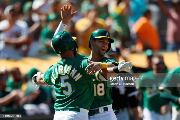 Chad Pinder of the Oakland Athletics is congratulated by Chris Herrmann after scoring the game winning run against the Chicago White Sox during the...