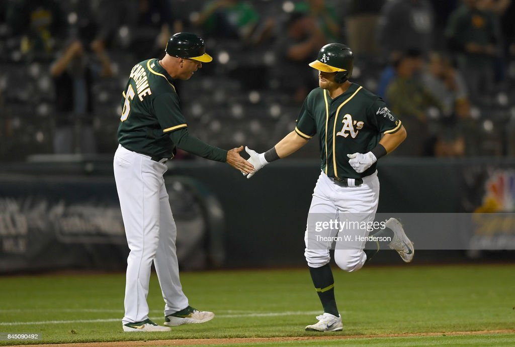 Chad Pinder #18 of the Oakland Athletics is congratulated by third base coach Steve Scarsone #15 after Pinder hit a solo home run against the Houston Astros in the bottom of the seventh inning of the second game in a double header at Oakland Alameda Coliseum on September 9, 2017 in Oakland, California.