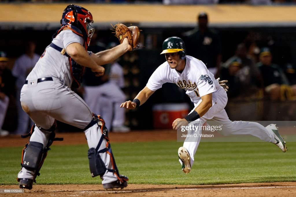 Chad Pinder #18 of the Oakland Athletics is tagged out at home plate by Evan Gattis #11 of the Houston Astros during the sixth inning at the Oakland Coliseum on June 19, 2017 in Oakland, California. The Houston Astros defeated the Oakland Athletics 4-1.