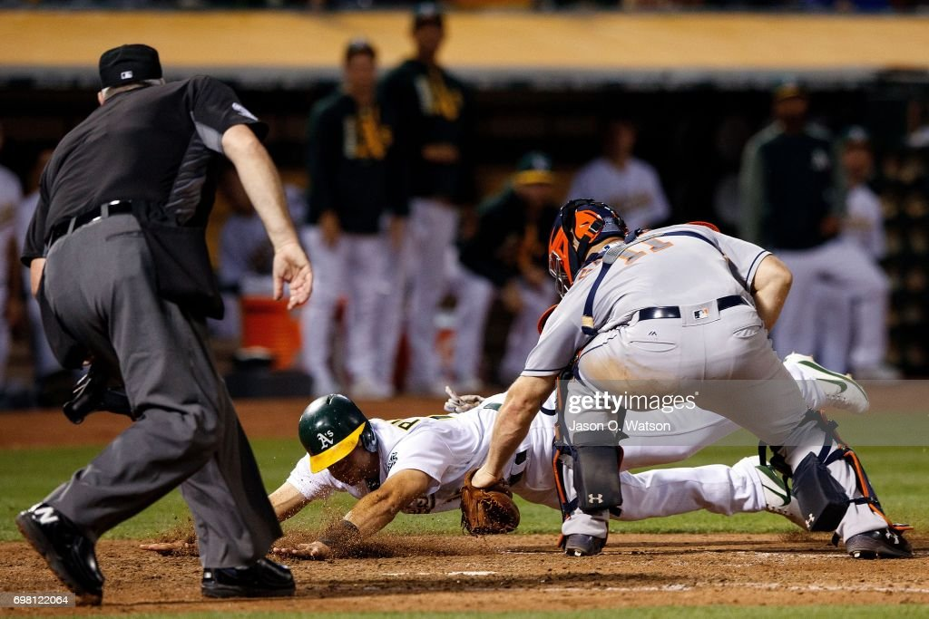Chad Pinder #18 of the Oakland Athletics is tagged out at home plate by Evan Gattis #11 of the Houston Astros in front of umpire Tim Welke #3 during the sixth inning at the Oakland Coliseum on June 19, 2017 in Oakland, California. The Houston Astros defeated the Oakland Athletics 4-1.