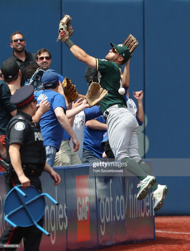 Chad Pinder #18 of the Oakland Athletics jumps into the seats in pursuit of a foul ball but cannot make the catch in the third inning during MLB game action against the Toronto Blue Jays at Rogers Centre on May 20, 2018 in Toronto, Canada.