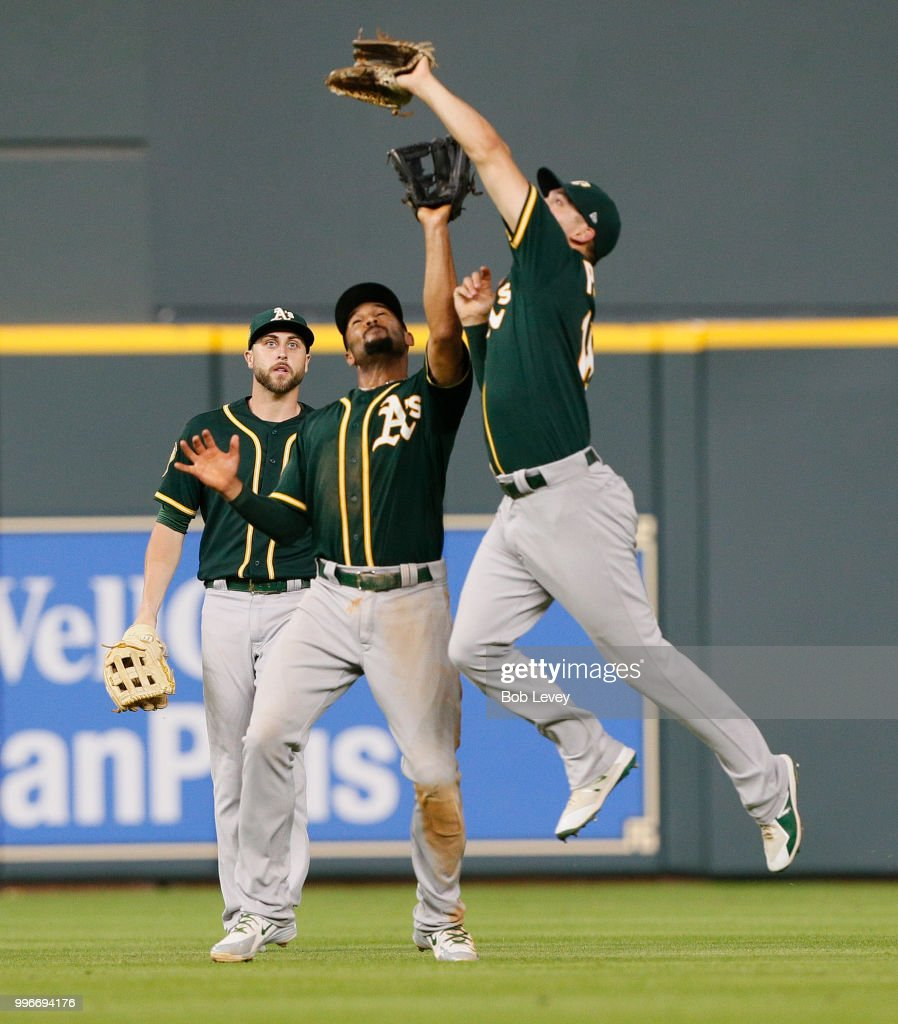Chad Pinder #18 of the Oakland Athletics makes catch over Marcus Semien #10 as Dustin Fowler #11 looks on against the Houston Astros at Minute Maid Park on July 11, 2018 in Houston, Texas.