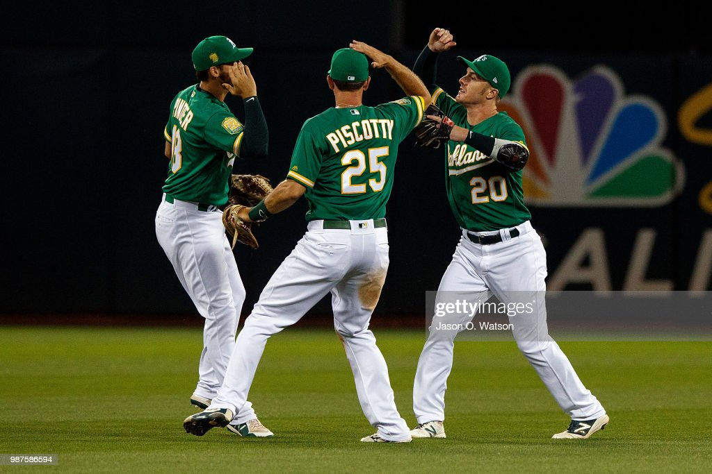 Chad Pinder #18 of the Oakland Athletics, Stephen Piscotty #25 and Mark Canha #20 celebrate after the game against the Cleveland Indians at the Oakland Coliseum on June 29, 2018 in Oakland, California. The Oakland Athletics defeated the Cleveland Indians 3-1.