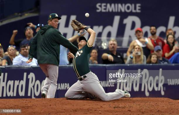 Chad Pinder of the Oakland Athletics trips over the bullpen mound and fails to catch a foul ball from Jake Bauers of the Tampa Bay Rays in the ninth...
