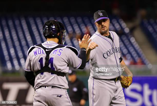 Chad Qualls of the Colorado Rockies high fives catcher Tony Wolters after finishing a game against the Philadelphia Phillies at Citizens Bank Park on...