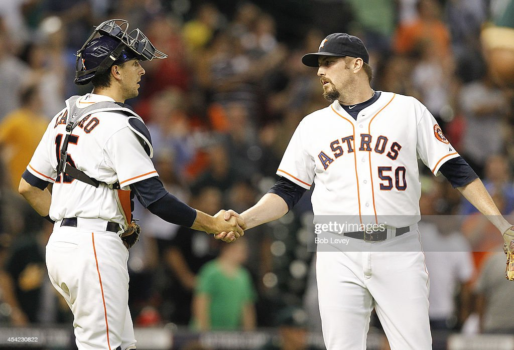 Chad Qualls #50 of the Houston Astros shakes hands with Jason Castro after the final out in a 4-2 win over the Oakland Athletics at Minute Maid Park on August 26, 2014 in Houston, Texas.